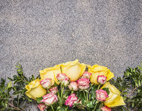 Bouquet of yellow and pink spring shrub roses border ,place for text wooden rustic background top view close up Stock Photography