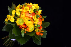 Bouquet yellow ranunkulyus with green leaves on black background Stock Images
