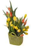 Bouquet of yellow and red tulips in a green vase Royalty Free Stock Photos