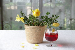 A bouquet of yellow roses and a glass of wine. A bouquet of yellow roses in decorative pot and a glass of wine Royalty Free Stock Photos