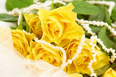 Bouquet of yellow roses and pearls on white dress Royalty Free Stock Image