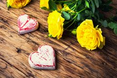 Spring flowers and symbolic red hearts. Bouquet of yellow roses and symbolic red hearts.Postcard for Valentine Day Royalty Free Stock Photography
