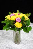 Bouquet of yellow roses with three purple in the glass vase Royalty Free Stock Images