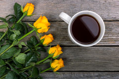 Bouquet of yellow roses and white cup of coffee on wooden background. A semicircular glare. Royalty Free Stock Image