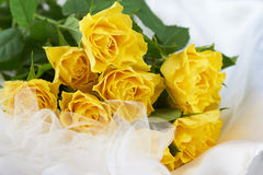 Bouquet of yellow roses on white dress. Bouquet of beautiful yellow roses on a white dress Royalty Free Stock Photo