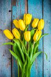 Bouquet of yellow tulips on a blue rustic background Royalty Free Stock Images