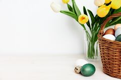 a bouquet of yellow tulips and Easter eggs pictures on a light table indoors