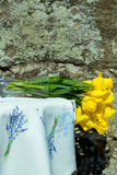 Bouquet of yellow tulips. In glass vase lies on side on embroidered tablecloth on sunny day on rock background Stock Photo