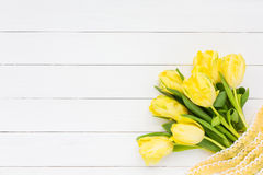 Bouquet of yellow tulips with ribbon  on white wooden background. Top view Stock Images
