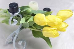 A bouquet of yellow tulips is scattered on a light surface. Nearby are decorative candles. Close-up, top view. A bouquet of yellow tulips is scattered on a Stock Image