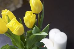 A bouquet of yellow tulips stands in a glass vase wrapped in a red ribbon tied to a bow. Nearby are decorative candles. Close-up,. Top view Stock Photos
