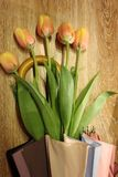 Bouquet of yellow tulips. In a umbrella on a wooden background Stock Images