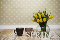 A bouquet of yellow tulips in a vase on the floor. A gift to a w Royalty Free Stock Photo