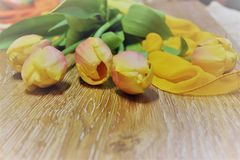 Bouquet of yellow tulips with a yellow handkerchief. Still-life of yellow tulips with a yellow handkerchief on a wooden background with a free space for your Stock Images