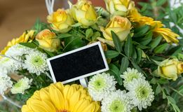 Bouquet with yellow and white roses. Gerbera, chrysanthemums and small blackboard with copy space Stock Photo