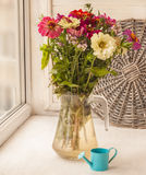 Bouquet  of zinnias   in a glass jar and  decorative  watering Royalty Free Stock Photo