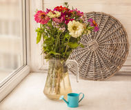 Bouquet  of zinnias   in a glass jar and  decorative  watering Royalty Free Stock Photography