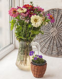 Bouquet  of zinnias   in a glass jar and  decorative  watering Royalty Free Stock Photos
