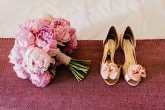 Bouquete van pioenen en mooie schoenen op roze achtergrond Huwelijk bouquete en schoenen met hoge hielen Bruid` s toebehoren Wedd royalty-vrije stock fotografie