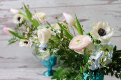 Bouquets of fresh flowers. Two Bouquets of ranunculus, anemones and other fresh flowers in two blue vases stands on the background of vintage floor Royalty Free Stock Photos