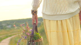 Bouquets of wild flowers in basket and woman hand holding it close up slow motion. stock footage