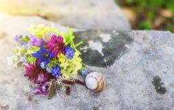 Bouquette av blommor och en snigel på en stor grå stenblock royaltyfria foton