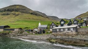 Bour, typical nordic village overlooking a fjord surrounded by green mountains, Faroe Islands