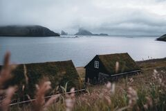Bour village Grass-covered picturesque houses at the Faroese coastline in the village Bour with view onto Dranganir and