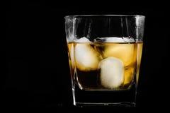 Bourbon. Glass of bourbon on black stock image