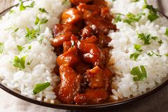 Bourbon chicken with garnish of rice close-up. horizontal. Bourbon chicken with garnish of rice close-up on a plate. horizontal royalty free stock images