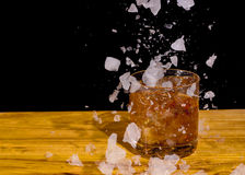 Bourbon in a glass with ice falling into it Stock Photos