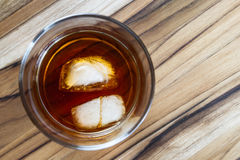 Bourbon with ice. 2 ice cubes floating in a glass with Kentucky straight Bourbon, served on a wooden table Stock Photo