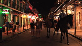 Bourbon Street New Orleans Mounted Police. Looking down world famous Bourbon Street in New Orleans, Louisiana. With two mounted police officers and tourists stock video