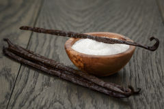 Bourbon vanilla pods with white sugar on wood table Royalty Free Stock Photography