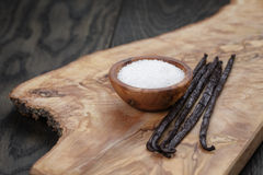 Bourbon vanilla pods with white sugar on wood table. Simpe dark photo Royalty Free Stock Photo