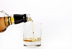 Bourbon whiskey. Glass pouring alcohol royalty free stock photo
