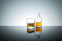 Bourbon whiskey on the rocks. In glass bottle on reflective surface white background backlit stock photo