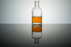 Bourbon whiskey on the rocks. In glass bottle on reflective surface white background backlit stock photography