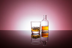 Bourbon whiskey on the rocks. In glass bottle on reflective surface white background backlit royalty free stock image