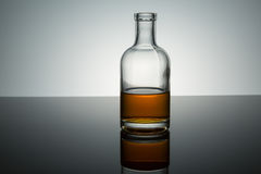 Bourbon whiskey on the rocks. In glass bottle on reflective surface white background backlit stock images