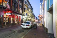 Bourbonstraat in schemering met politiewagen Stock Foto's