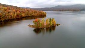 Bourdon aérien - mouche au-dessus de lac vers la petite île remplie d'arbres de couleur d'automne au Vermont banque de vidéos