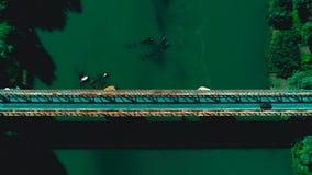 Bourdon aérien tiré : voler en avant le long des véhicules croisant le pont en route au-dessus d'une rivière Vue supérieure banque de vidéos