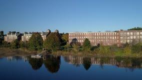 Bourdon aérien - vieille usine de textile de Pan Over Mirror Lake Across à Exeter, New Hampshire 4K banque de vidéos