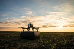 bourdon avec le vol d'appareil photo numérique en ciel au-dessus de champ sur le coucher du soleil Photographie stock
