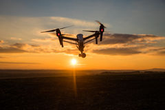 bourdon avec le vol d'appareil photo numérique en ciel au-dessus de champ sur le coucher du soleil Image libre de droits