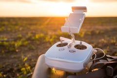 bourdon avec le vol d'appareil photo numérique en ciel au-dessus de champ sur le coucher du soleil Photos libres de droits