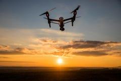 bourdon avec le vol d'appareil photo numérique en ciel au-dessus de champ sur le coucher du soleil Image stock