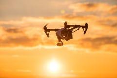 bourdon avec le vol d'appareil photo numérique en ciel au-dessus de champ sur le coucher du soleil Photo libre de droits