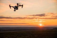 bourdon avec le vol d'appareil photo numérique en ciel au-dessus de champ sur le coucher du soleil Photos stock